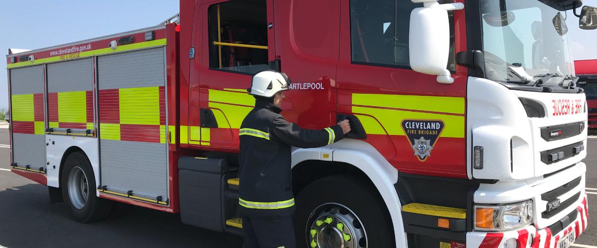 firefighter opening door of fire engine