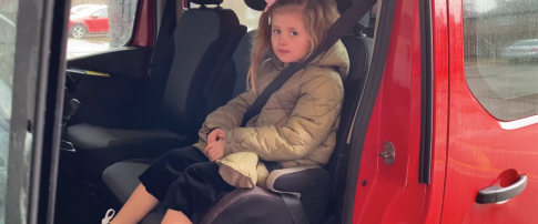 girl wearing seat belt and sitting in car seat