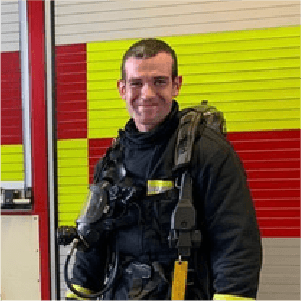 tim taylor on call fire fighter stood infront of fire engine
