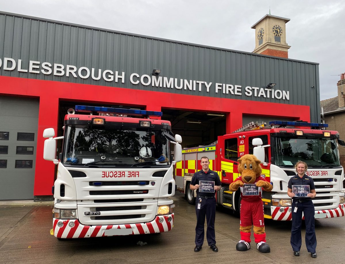 Firefighters and MFC mascot roary the lion stood outside Middlesbrough Fire station holding key safety messages.